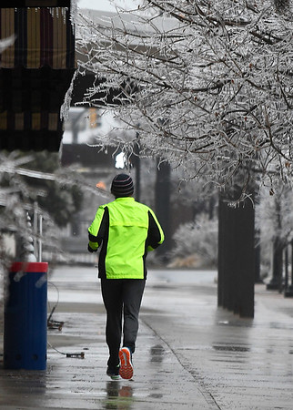 A man jogs under ice covered trees in downtown Enid Sunday January 15, 2017. (Billy Hefton / Enid News & Eagle)