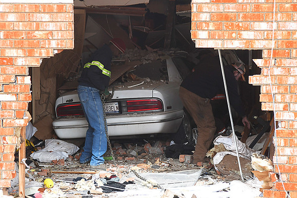 The resident at 201 N. McKinley (right) picks through his belongings as a tow truck drives attaches a chain to a car that drove into the house Wednesday January 18, 2017. (Billy Hefton / Enid News & Eagle)