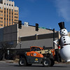 The snowman from the courthouse square is hauled through downtown by a forklift Wednesday January 4, 2017 to it's resting place until next holiday season. (Billy Hefton / Enid News & Eagle)