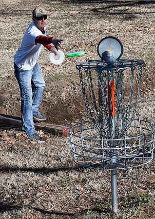 Matt Martin tosses his disc into a basket while playing a round at the NWOSU Enid course Friday January 27, 2017. (Billy Hefton / Enid News & Eagle)