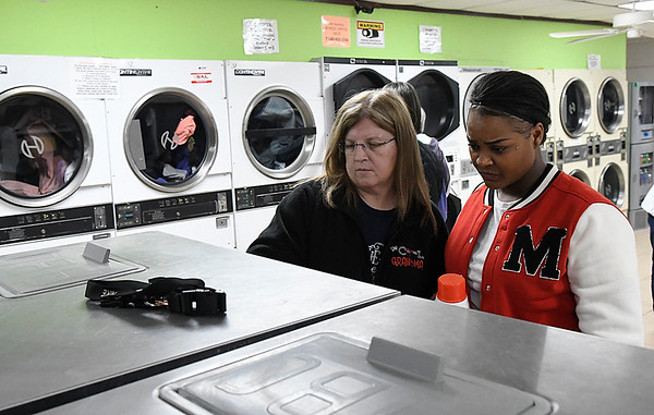 Shari Benson (left), from the Enid First Baptist Church, pays for a load of laundry for Ameshia Lofton during Laundry Love at the Maine Street Coin Laundry Tuesday January 9, 2017. (Billy Hefton / Enid News & Eagle)