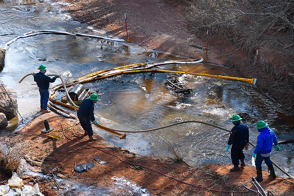 Members of a clean up crew get a hose in place as they work an oil spill in Black Bear Creek on South Knox Road between Rupe and Southgate in eastern Garfield county Thursday January 31, 2019. (Billy Hefton / Enid News & Eagle)