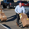 Cory Moore and Brad Blankenship, from Security National Bank, wheel in school supplies to Coolidge Elementary Monday January 7, 2018. Security National Bank donates supplies to one school at mid-term each year. (Billy Hefton / Enid News & Eagle)