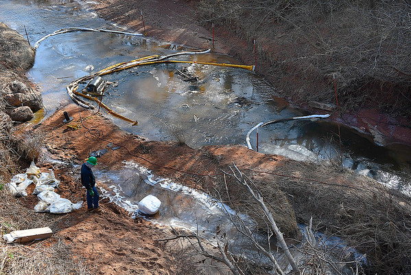 A member of an oil spill clean up crew stands on the bank of Black Bear Creek on South Knox Road between Rupe and Southgate in eastern Garfield county Thursday January 31, 2019. (Billy Hefton / Enid News & Eagle)
