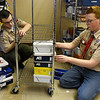 Joseph Bamberg (right) and Austyn Neely fill a rack with shoes for the Foster Feet program as part of Bamberg's Eagle Scout project Thursday January 3, 2019 at Central Christian Church. (Billy Hefton / Enid News & Eagle)