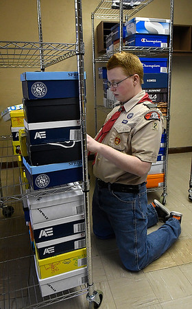 Joseph Bamberg fills a rack with shoes for the Foster Feet program as part of his Eagle Scout project Thursday January 3, 2019 at Central Christian Church. (Billy Hefton / Enid News & Eagle)