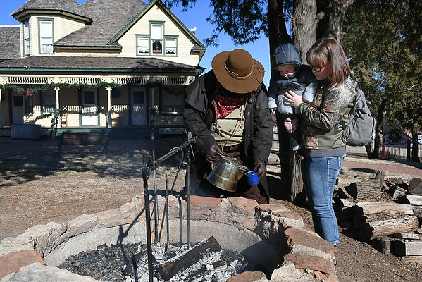 Casey Young holds her son, Roman,Tom Lentz pours a cup of coffee at Humphrey Heritage Village Saturday, January 4, 2020. (Billy Hefton / Enid News & Eagle)