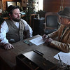 Jake Krumwiede (left) and Glen Haworth act out registering a claim inside the Enid Land Office at Humphrey Heritage Village Saturday, January 4, 2020. (Billy Hefton / Enid News & Eagle)