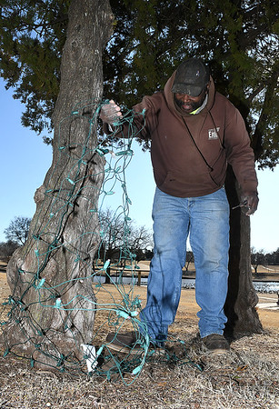 Lemuel Harris, of the City of Enid Parks Dept., removes Christmas lights from a tree at Meadowlake Park Friday, January 3, 2020. (Billy Hefton / Enid News & Eagle)