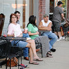 A young boy sleeps on his mother's shoulder (back, far left) as Five80 customers enjoy the grand opening of the new Enid business during First Friday festivities in downtown Enid Friday, July 5, 2013. (Staff Photo by BONNIE VCULEK)