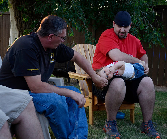 """Waukomis Chief of Police Robert Sach, left, talks to Phillip Ott, right, and his daughter Anndi during the Waukomis Fire Department's gathering Thursday, July 4, at Fire Chief Clarence Maly's house. The fire department is a """"close-knit"""" group, said Mason Hornberger, the assistance training officer. (Staff Photo by JESSICA SALMOND)"""