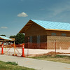 A man walks pass the restrooms and pavilion under construction on the Enid Trail System near Cleveland Street. (Staff Photo by BILLY HEFTON)