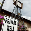 The residence at the corner of Cherokee and Hayes displays it's private well sign Wednesday. The city of Enid began it's water rationing program July 16. (Staff Photo by BILLY HEFTON)
