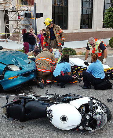 The rider of a motorcycle is treated by Enid emergency personnel after she was involved in a motorcycle vs car at the intersection of Randolph and Grand Wednesday. (Staff Photo by BILLY HEFTON)