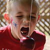 Taryn Ashlosk, 5, tried to get the apple without using his hands at the Hometown Celebration on Wednesday, July 4, at Leonardo's Adventure Quest. Over 300 people attended the festivities from 10 a.m. to noon. (Staff Photo by JESSICA SALMOND)