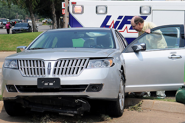 Dan Dillingham checks on the driver of a Lincoln MKS after a two-vehicle collision at the corner of Willow and Cleveland Monday, July 1, 2013. (Staff Photo by BONNIE VCULEK)