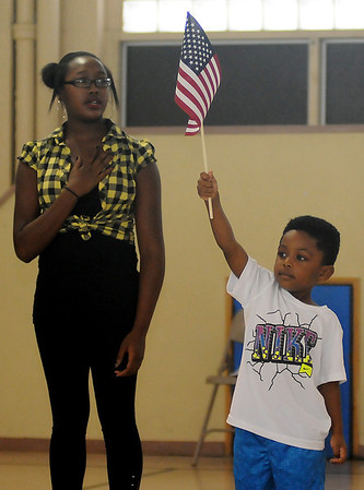 Adrian Montgomery (right) proudly holds an American flag during the Pledge of Allegiance at the Booker T. Washington Community Center summer camp show Friday, July 26, 2013. (Staff Photo by BONNIE VCULEK)