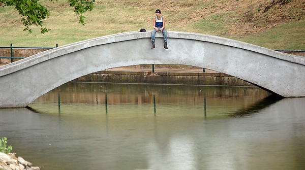 A young fisherman doesn't let a rain shower deter his efforts Wednesday at Government Springs Park. (Staff Photo by BILLY HEFTON)