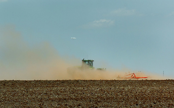 A tractor is obscured by the dust it is creating as it plows a field along south Wheat Ridge Tuesday. (Staff Photo by BILLY HEFTON)