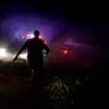 Waukomis Fire Department Lieutenant Bobby Kokojan walks through the smoke of a small grass fire to talk to the other Waukomis truck Thursday, July 4. (Staff Photo by JESSICA SALMOND)