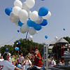 Whitney Box (center) watches a bunch of balloons lift into the air to signal the official opening of Champions Park Sunday. (Staff Photo by BILLY HEFTON)