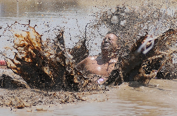 A Muddy Badgers player sacrifices his body for a return during championship action against the Rum Boats at the 2nd annual Miracle League Mud Volleyball Tournament at the Chisholm Trail Expo Center Saturday, July 13, 2013. (Staff Photo by BONNIE VCULEK)