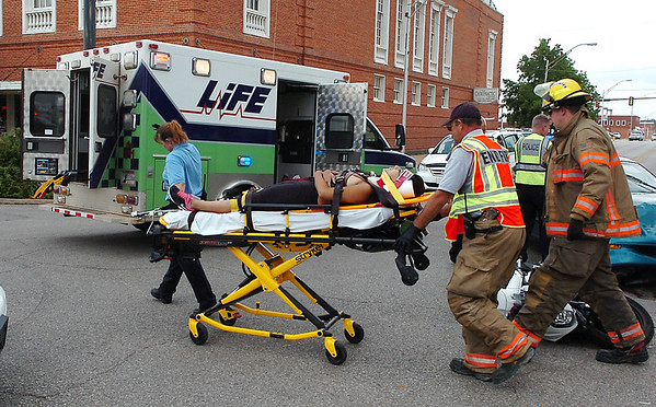 The rider of a motorcycle is moved to an ambulance by Enid emergency personnel after she was involved in a motorcycle vs car at the intersection of Randolph and Grand Wednesday. (Staff Photo by BILLY HEFTON)