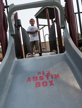 #12 Austin Box appears on one of the slides as William Stading plays at Champion Park Friday, July 5, 2013. Whitney Box, an older sister of Enid High School star athlete and University of Oklahoma football linebacker Austin Box, designed the new park with the assistance of the Austin Box Foundation and the City of Enid. The grand opening of the facility is slated for 11 a.m. Sunday, July 9, 2013 at the corner of 10th and Chestnut. (Staff Photo by BONNIE VCULEK)