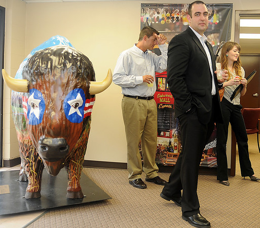 Prairie Thunder (left), created by artist Cindy Van Kley and sponsored by the Ward Petroleum Corporation, greets guests as they enter the new Visit Enid Welcome Center at 201 W. Owen K. Garriott for the grand opening of the new location Tuesday, July 30, 2013. Among the guests were Rick Hontz (center), regional vice-president of Global Spectrum, Keller Taylor, general manager of the Enid Event Center and Convention Hall, and Rynn Day. (Staff Photo by BONNIE VCULEK)