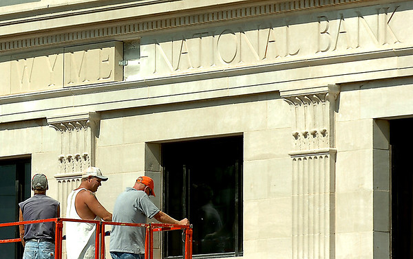 Crew members lower their scissor lift Monday while replacing the First National Bank name on 1 Grand Place Monday. (Staff Photo by BILLY HEFTON)