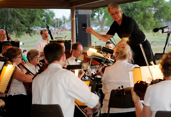 Douglas Newell directs the Enid Symphony Orchestra at Meadowlake Park during the Fourth of July festivities Thursday, July 4, 2013. (Staff Photo by BONNIE VCULEK)