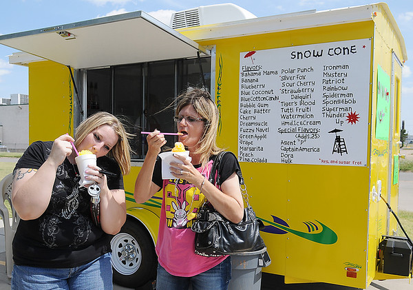 Summer Fletcher and Rena Chaplin devour their sweet treats from E-Town Ice Tuesday, July 9, 2013. The new shaved ice business, which opened in The Commons' parking lot Tuesday, July 2, features regular and sugar free flavors at the corner of Oakwood Road and King Street. (Staff Photo by BONNIE VCULEK)
