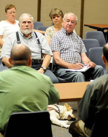 Ralph Haney's seeing-eye dog rests near him as concerned citizens listen to James Neal, general manager of the Enid Public Transit Authority, explain the proposed changes in the EPTA operations, services and fare rates during a public forum at the City of Enid Commission Chambers Wednesday, July 10, 2013. (Staff Photo by BONNIE VCULEK)