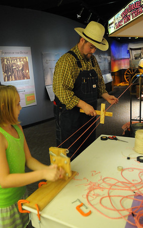 Alexis Owens (left) and Cody Joliff, educational director for the Cherokee Strip Regional Heritage Center, demonstrate how to make a twisted rope during Pioneer Day at the museum Saturday, July 6, 2013. (Staff Photo by BONNIE VCULEK)