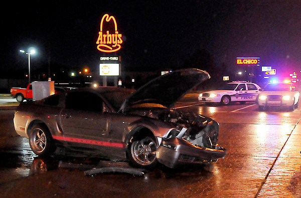 A Mustang sits in the intersection of Oakwood and Garriott Monday evening after being involved in a two-vehicle accident. (Staff Photo by BILLY HEFTON)