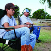 Colton Williams, 12, left, waits for a bite with his father, Shannon Williams, right, at the fishing derby on July 4 at Meadowlake Park. Going to the fishing derby is a tradition for Shannon and Colton. (Staff Photo by JESSICA SALMOND)