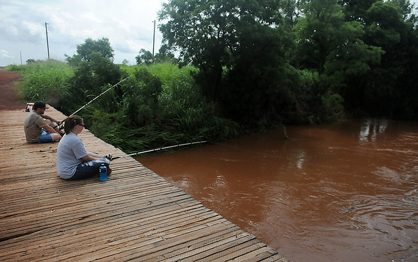 Brent and Ericka O'Donnell fish off a rural county bridge near 77th and Wood Road Tuesday, after thunderstorms dropped an additional 2-5 inches across Garfield County Tuesday, July 30, 2013. (Staff Photo by BONNIE VCULEK)