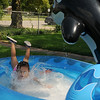 Cameron Dean, 3-year-old daughter of Marissa Bell and David Dean from Enid, dives into her private kiddie pool with her tennis shoes on as she cools off Tuesday, July 23, 2013. Dean looks forward to her daily swims and tea parties. (Staff Photo by BONNIE VCULEK)