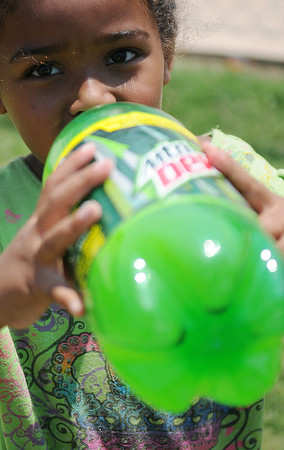 Unika Revels cools off with a drink of Mountain Dew Friday, July 5, 2013. (Staff Photo by BONNIE VCULEK)