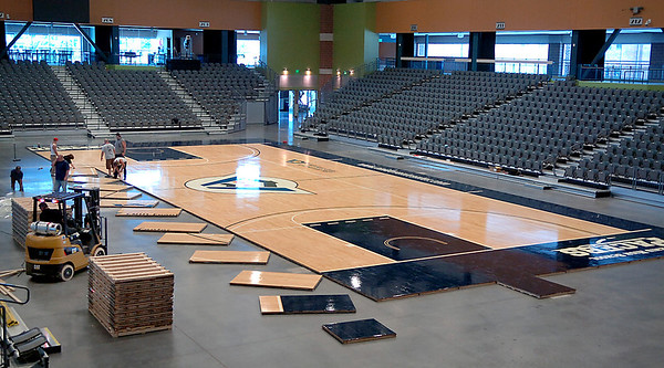 An Enid Event Center crew assembles the new basketball floor Monday. The floor consist of 200 sections and weighs 44,000 pounds. (Staff Photo by BILLY HEFTON)