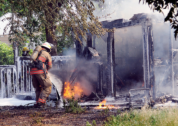 Lt. Patrick Parrish flips over a wood panel as Enid firefighters extinguish a 10 x 12 shed fire at 615 E. Broadway Monday, July 1, 2013. When firefighters arrived on the scene, the shed was fully involved. (Staff Photo by BONNIE VCULEK)