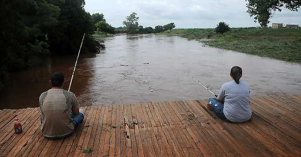 Brent and Ericka O'Donnell fish above a rain-swollen creek Tuesday, July 30, 2013. An additional 2-5 inches of rain caused flooding in several rural areas of Garfield County. (Staff Photo by BONNIE VCULEK)