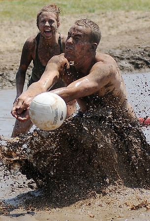 Rum Boat players dig for a return against the Muddy Badgers during the 2nd annual Miracle League Mud Volleyball Tournament at the Chisholm Trail Expo Center Saturday, July 13, 2013. (Staff Photo by BONNIE VCULEK)