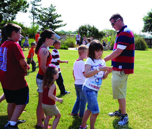Intern Trent Misak hands out prizes after a relay race during the Hometown Celebration on Wednesday, July 4, at Leonardo's Adventure Quest. Trent and Dani Comstock, the other intern, organized this year's event. (Staff Photo by JESSICA SALMOND)