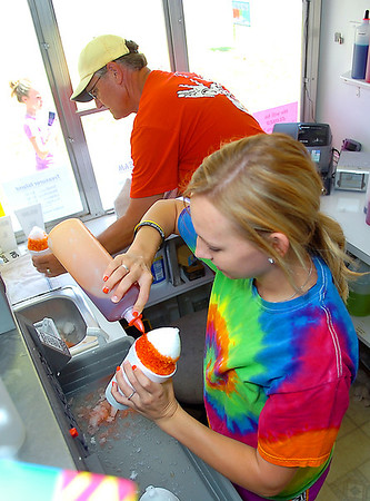Sydney Postier makes a sno cone as her dad, Kevin, tends the window Sunday at Treasurer Island. (Staff Photo by BILLY HEFTON)