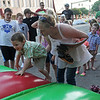 Jolene Jones helps her son, Kerry Mac, onto an inflatable toy during First Friday festivities in downtown Enid Friday, July 5, 2013. (Staff Photo by BONNIE VCULEK)
