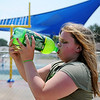 Alexandria Gentry, 12, refreshes herself with a cold drink of Mountain Dew as she plays with family and friends at the Splash Pad and Champion Park, near the intersection of 10th and Chestnut Friday, July 5, 2013. (Staff Photo by BONNIE VCULEK)
