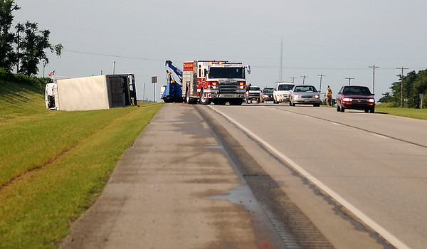 Enid Fire Department and Enid Police Department assist at the scene of a roll-over accident near the entrance to the Grayridge residential area and U.S. 81 early Wednesday, July 24, 2013. According to an initial report, the driver of a box truck was falling asleep behind the wheel, over-corrected, and rolled the vehicle. Occupants of the box truck kicked out the windshield of the truck and crawled to safety. (Staff Photo by BONNIE VCULEK)