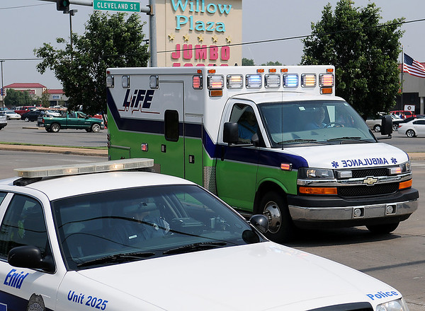 As Enid Police officers work the scene of an accident at the intersection of Willow and Cleveland Streets, Life EMS responds to a medical call in the Woodlands Monday, July 1, 2013. (Staff Photo by BONNIE VCULEK)