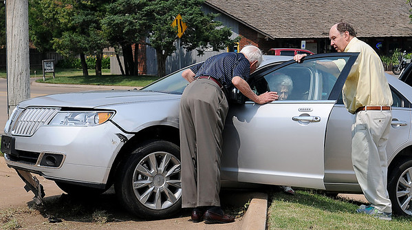 Earl Mabry M.D. (left) and Dan Dillingham visit with the driver of a Lincoln MKS after a two-vehicle crash at the intersection of Willow and Cleveland Monday, July 1, 2013. Enid Fire Department, Enid Police Department and Life EMS responded to the scene. (Staff Photo by BONNIE VCULEK)